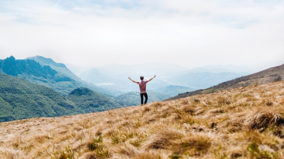 A man on a hilltop reaching out his arms with an open expanse before him