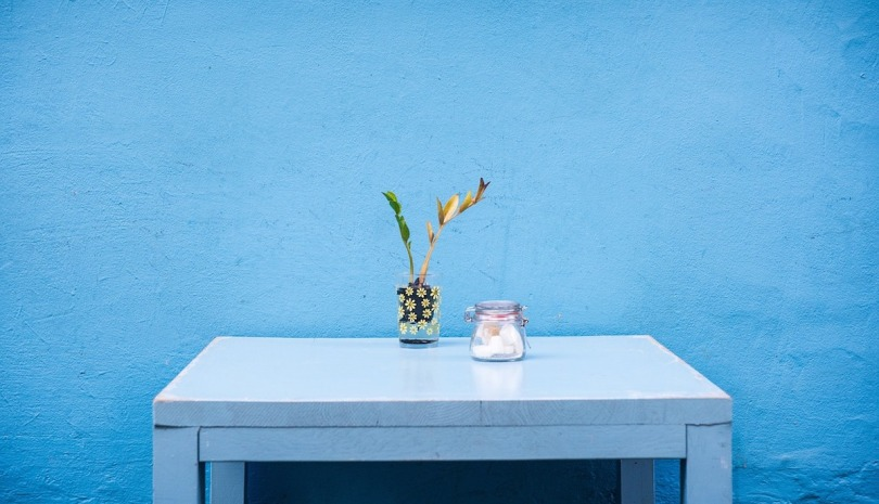 A blue table in front of a blue wall
