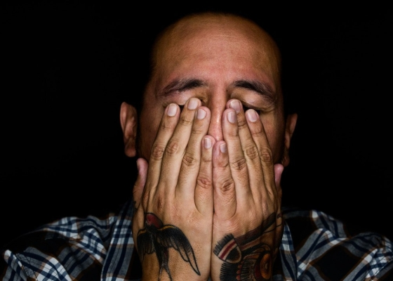 A tattooed man with his hands to his face