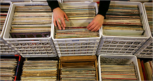 A person's hands as they look through boxes of vinyl records