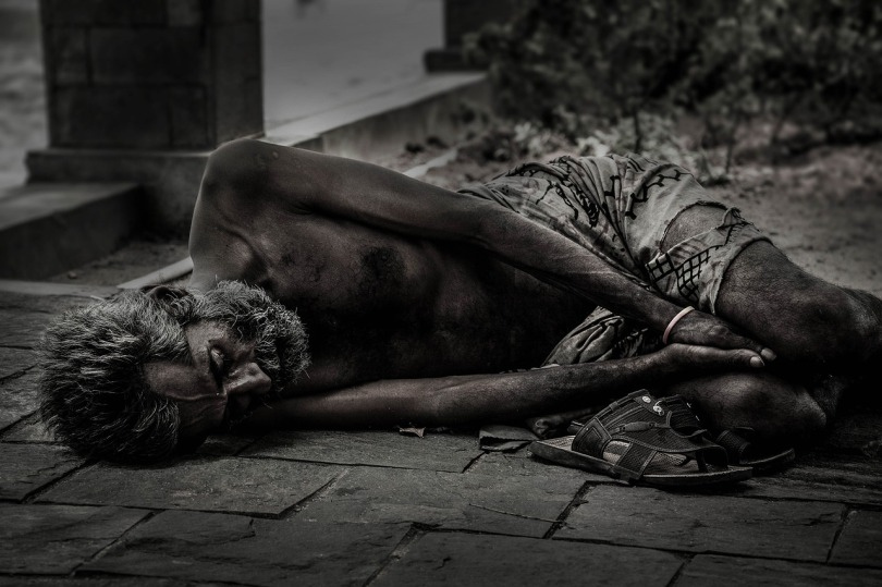 A black and white photo of a thin man lying on the pavement