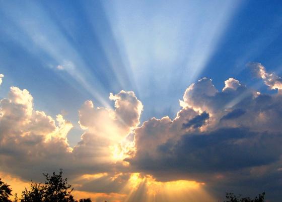 A photo of the sun bursting through a cloudy sky