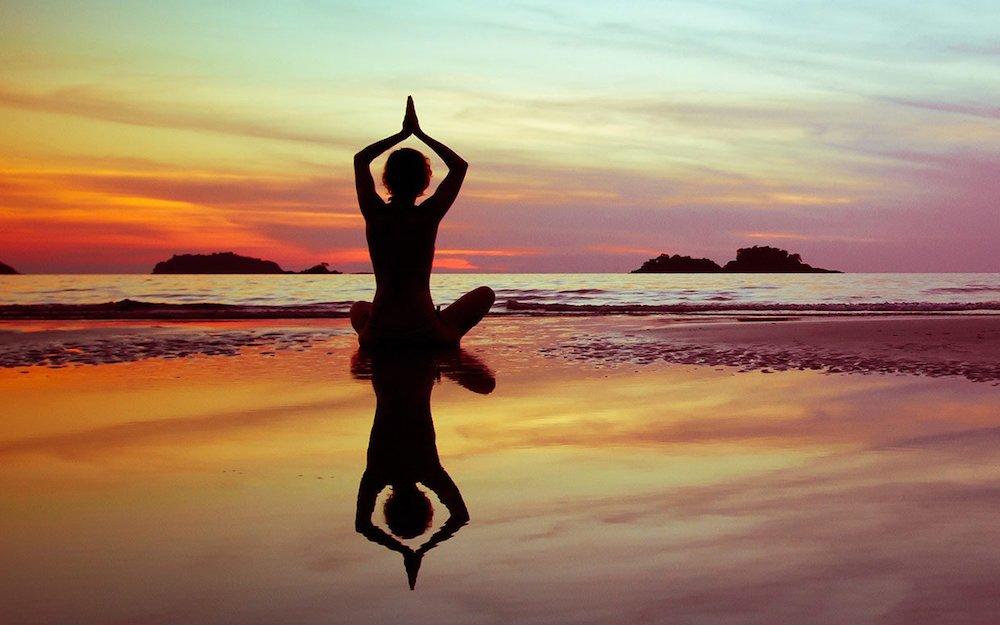 A person sat cross-legged in a yoga position on a beach