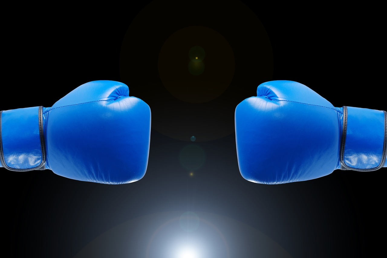 Blue boxing gloves with a black background