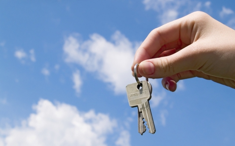 I hand holding keys with blue sky in the background