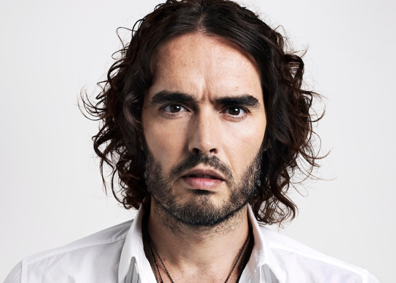 A headshot of Russell Brand with a white background