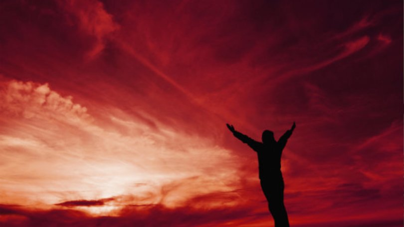 A person reaching out to the heavens with red sky in the background
