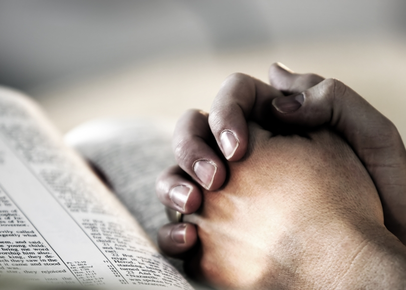 A person's hands joined together and leaning on a Bible