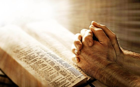 Hands locked together in prayer over a Bible