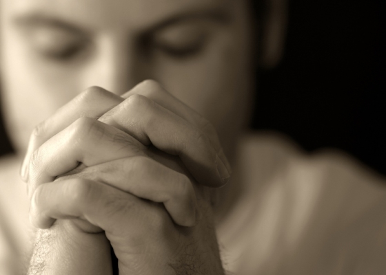 A man with his hands clasped together in prayer
