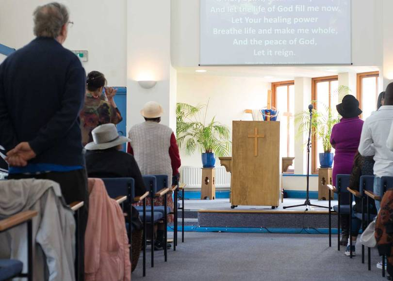 A picture inside East Hill Baptist Church with the congregation standing
