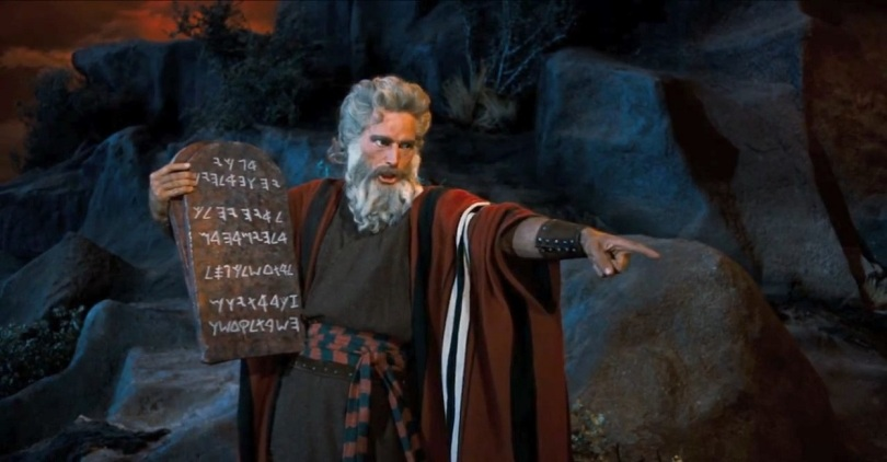 Moses holding a stone tablet and pointing