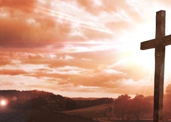 A wooden cross on the right beaming light to the cloudy orange sky behind it