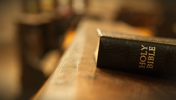 A Bible on a wooden surface with a blurry background