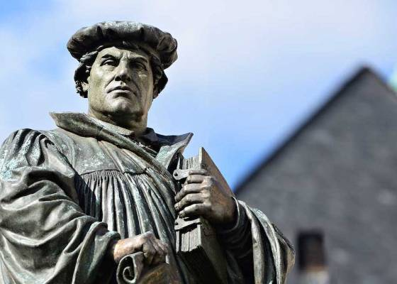 A statue of Martin Luther with a blue sky background
