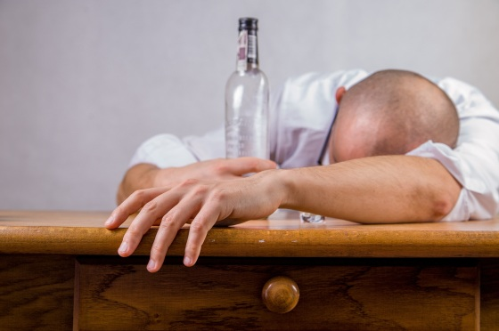 A man collapsed over a table with an empty bottle in his hand