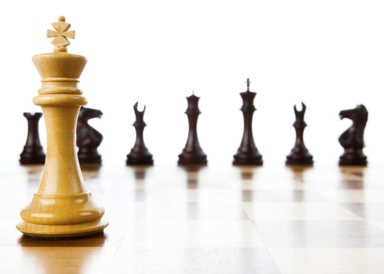 A chess board with a white king in the foreground and black pieces in the background