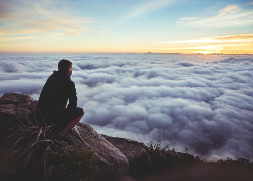 A man crouched down on a mountain top overlooking a bed of clouds