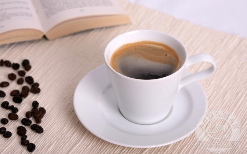 An Americano coffee on a table with a book and some coffee beans