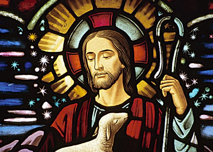 A stained glass picture of Jesus with a staff and a lamb