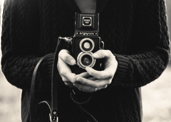 A closeup of a person holding an old-fashioned camera