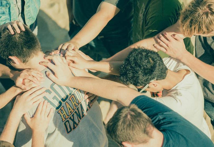 A group of Christians laying hands on a man and praying for him