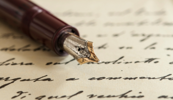 A gold-nibbed fountain pen resting on writing paper