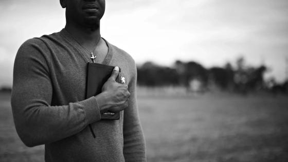 A dark-skinned man holding a Bible to his chest (black and white picture)