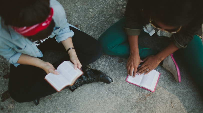 Two Christians sat on the ground reading their Bibles, shot from above