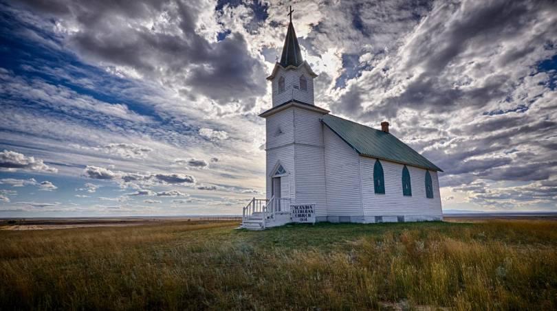 A quaint white church in a field on a cloudy day