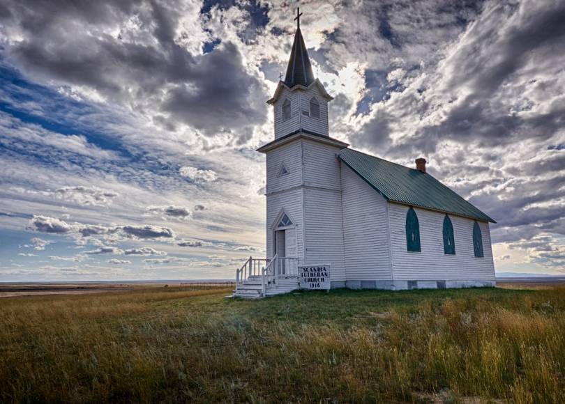 A quaint white church in a field on a cloudy day