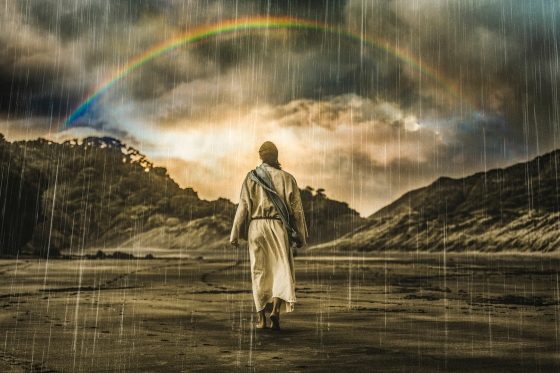 A man looking at a rainbow in the pouring rain