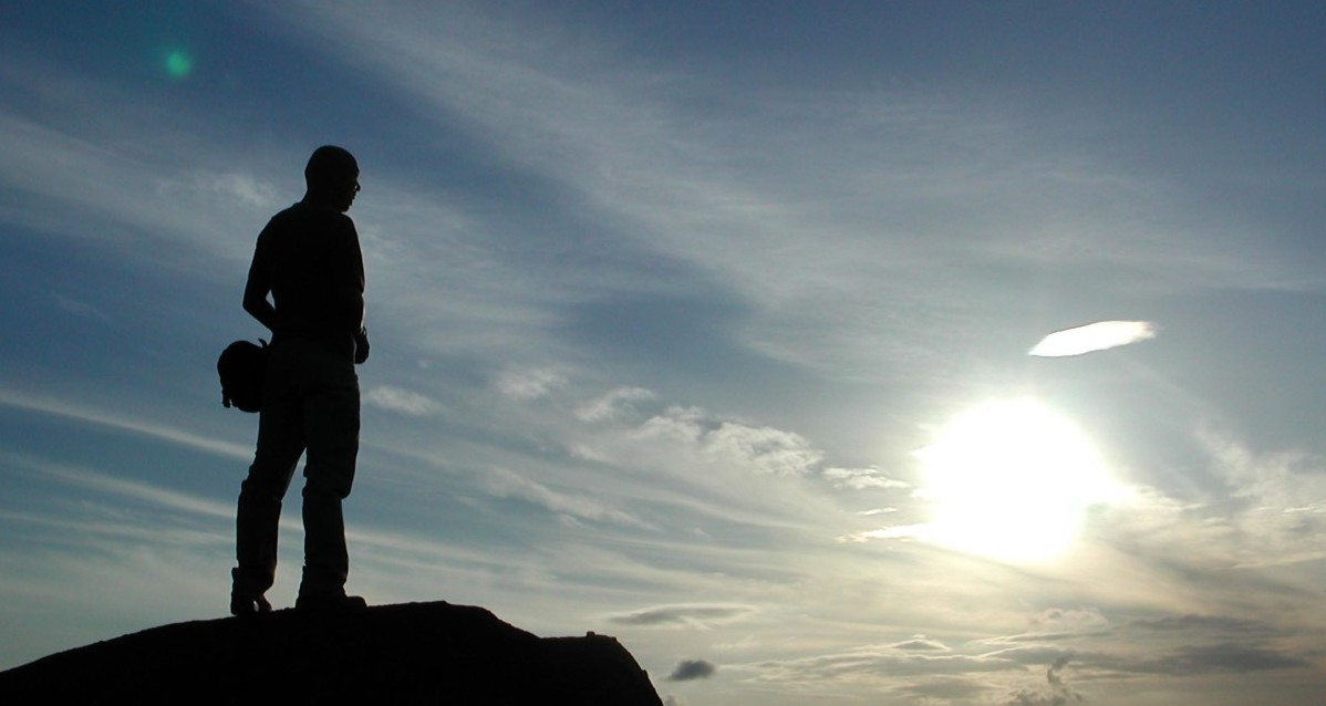 A man in silhouette stood on a rock looking at the sun in the distance