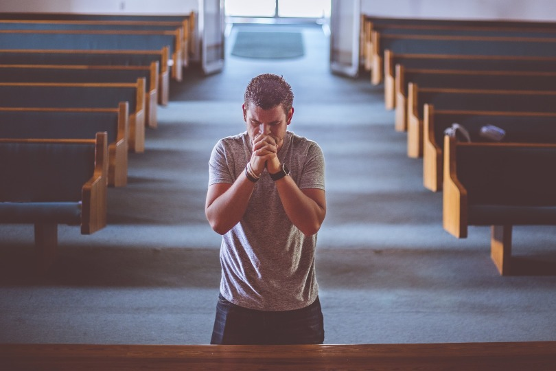 A man kneeling and praying at the front of an empty church