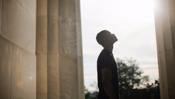 A dark-skinned man looking towards the heavens