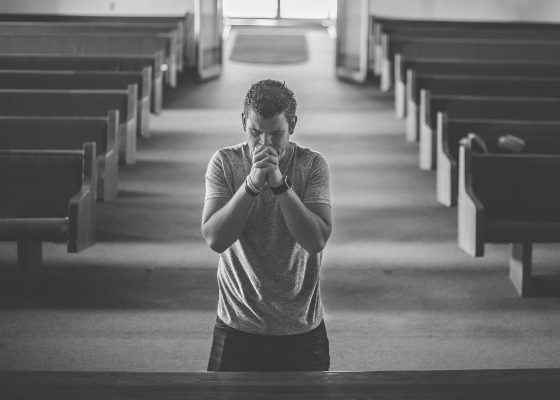 Man praying in church black and white