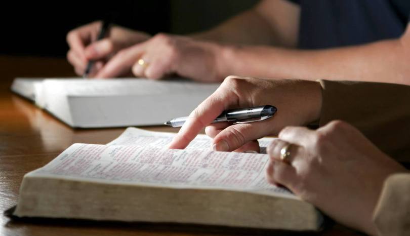 A closeup picture of two people annotating their Bibles