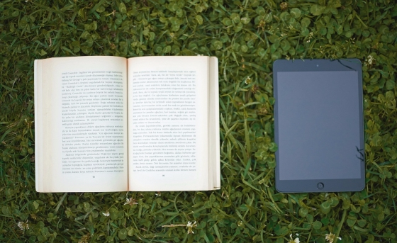 A book and a tablet laid out on the grass