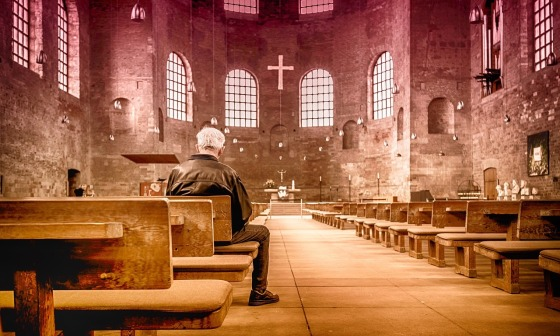 A man on his own sat in a large empty church