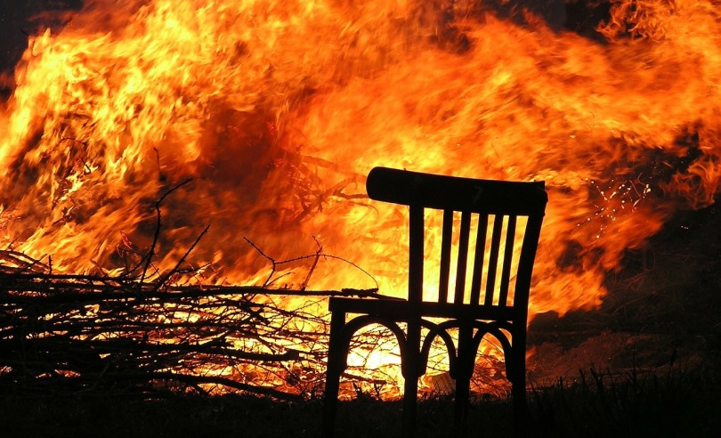 A chair in the foreground and a burning fire in the background