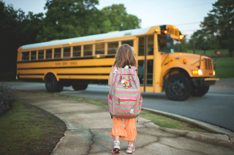 A young girl wearing a backpack looking at a yellow school bus