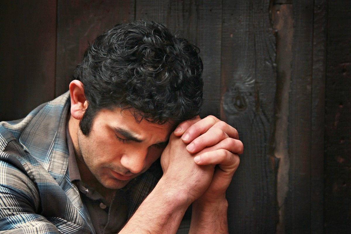 A man praying in front of a dark wooden wall