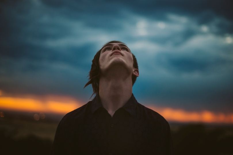 A man looking to the heavens with stormy weather in the background
