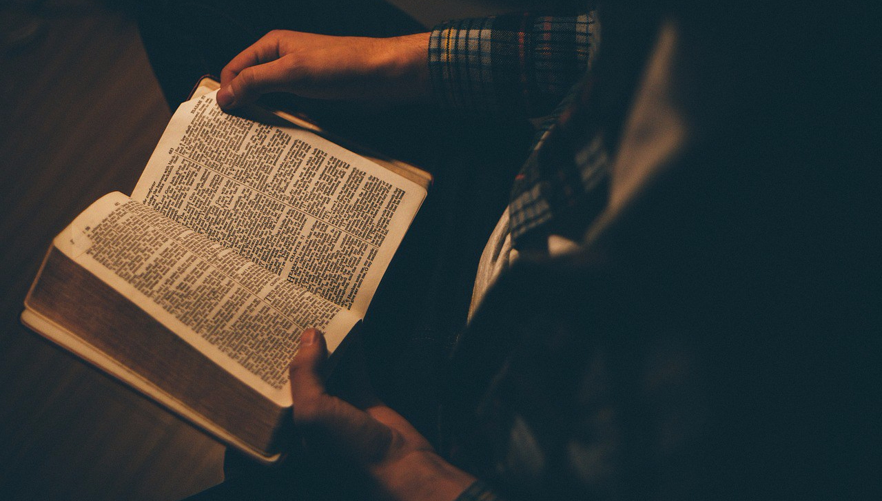 An image with low lighting of a man reading an open Bible