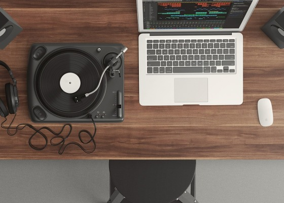 A MacBook and musical equipment on a wooden desk