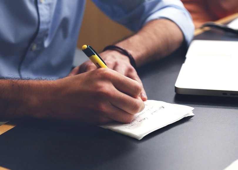 Man in a shirt making notes on a piece of paper