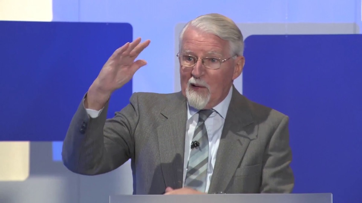 David Pawson delivering a talk and gesturing with his hand