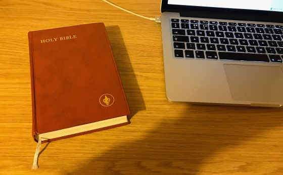 A Gideon Bible next to a laptop on a wooden table