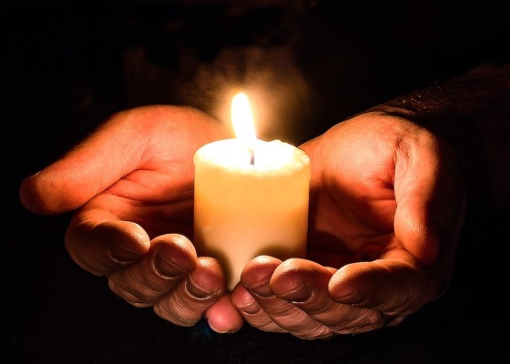 Two hands held out holding a white candle which contrasts with the dark background