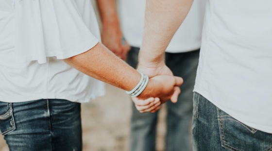 A closeup of two believers holding hands and wearing white t-shirts and jeans